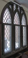 A triptychal window overlaid with diagonal grid paneling and stone tracery