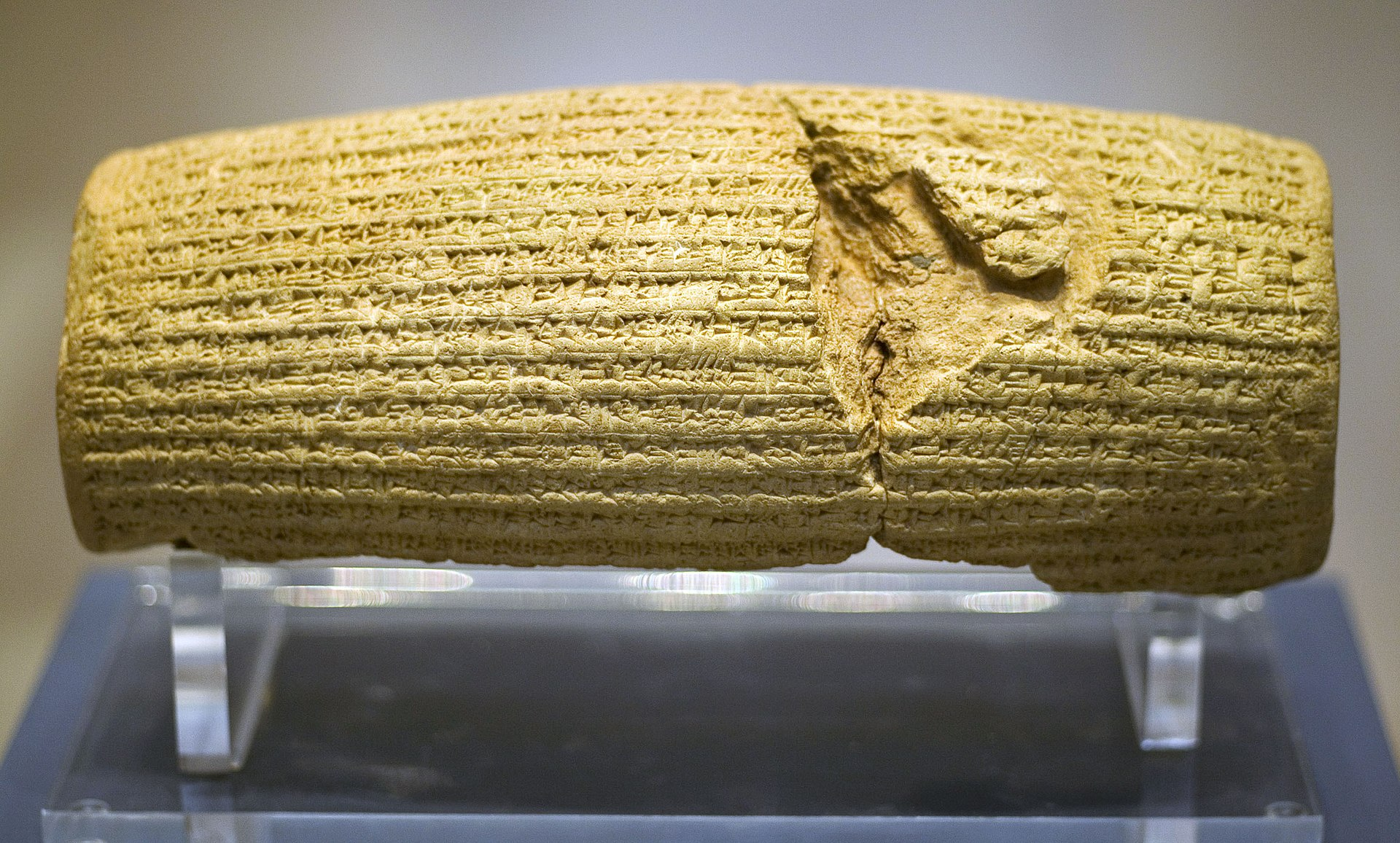 Front view of a barrel-shaped clay cylinder resting on a stand. The cylinder is covered with lines of cuneiform text