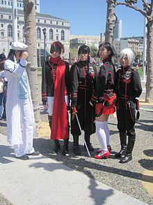 Five people doing cosplay of manga and anime series. While the first one is mostly dressed in white, the other four are dressed in black and red uniforms.
