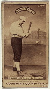 A baseball player is shown holding a baseball bat in the act of hitting a baseball
