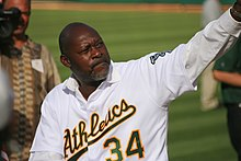 "A dark-skinned man wearing a white baseball jersey with ""Athletics"" across the chest in green script"