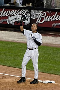 A man in a white baseball uniform with navy pinstripes removes his helmet to salute the crowd, which is cheering for him.
