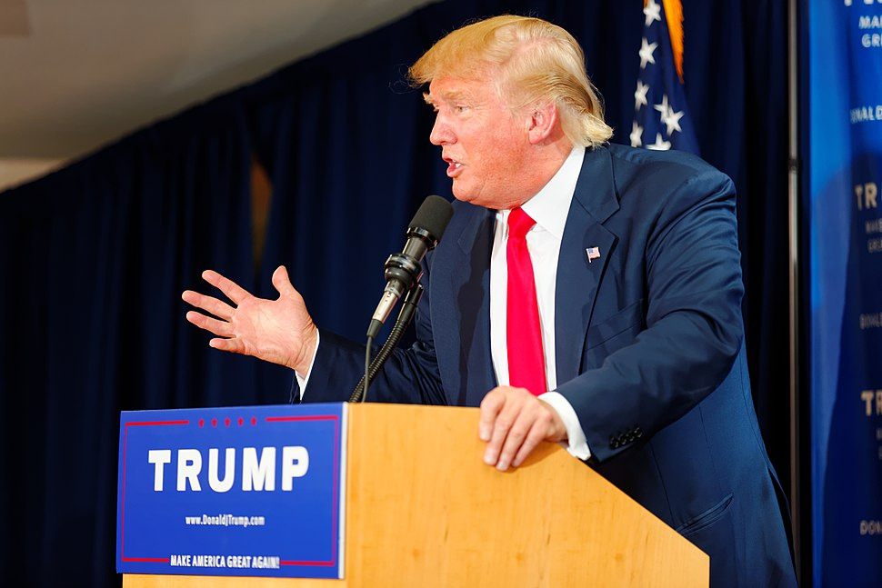 """Trump speaking behind a brown wooden podium, wearing a dark blue suit and a red tie. The podium sports a blue """"TRUMP"""" sign."""