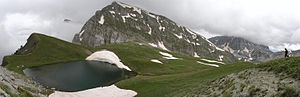 A small lake surrounded by alpine pasture with traces of snow and two mountain peaks in the background: center and right.