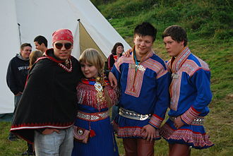 Luhkka - The musical group Duolva Duottar in traditional Sami dress.  The man on the left, Ole Mahtte Gaup, is wearing a luhkka. The woman and the other two men are wearing gákti.