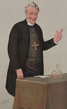 "A ""Spy"" cartoon of a clergyman with greying hair, parted to the right, wearing a black jacket and a large gold pectoral cross, standing behind a table with his left hand raised in blessing"