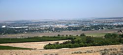 Finley shown with industrial complexes along Columbia River and orchards in the foreground