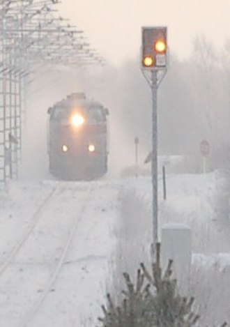 Railway signal - A Finnish distant signal at the western approach to Muhos station is displaying Expect Stop. In the background, express train 81 is pulling away from the station.