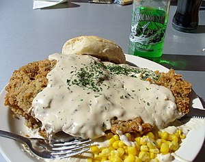 Chicken fried steak covered with gravy, corn (...