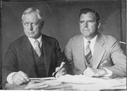 Photograph taken circa 1930 of Burnham with his son Roderick. Frederick Burnham is on the left, and Roderick Burnham is on the right. Both men are wearing suits and ties and they seated at a table with many papers in front of them.