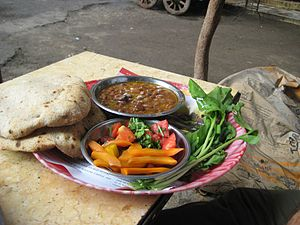 Ful medames - Typical fūl medames breakfast as served by an Egyptian street vendor with bread and pickled vegetables, as well as fresh rocket (arugula) leaves on the side.