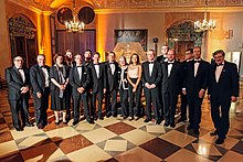 Group of men and women in evening dress ins a ballroom with a checkerboard floor