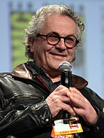 A grey haired man is seen wearing a black leather jacket.