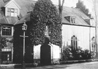A black and white photograph of the outside of a medieval school hall. The outside is covered in ivy.