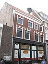 foto van Pand met lijst met natuurstenen blokken boven de vensters, bovendeel verhoogd, beneden verbouwd