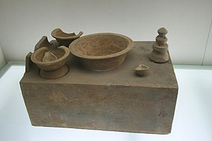 Wok - A Han dynasty Chinese stove model with cooking pots showing the basic attributes that derived to modern wok stoves.