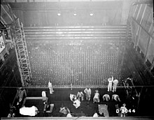 A photo taken from a ceiling of a tall square industrial room. Cement walls have metal ladders and meshes. A dozen of people are engaged in some activities on the floor.