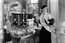 Albert carries an armful of boxes for Lillian