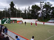 An indoor soccer game at an open-air venue in Mexico. The referee has just  awarded the red team a free kick.