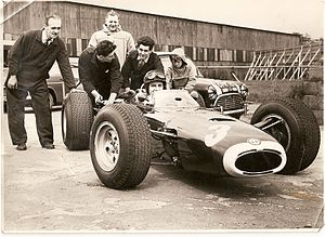 BRM P261 - Chassis designer John Crosthwaite (in the pale duffel coat) oversees BRM mechanics pushing driver Graham Hill out on to the track, during testing of a BRM P261
