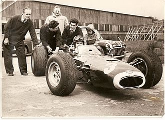 British Racing Motors - Graham Hill in BRM P261, testing at Silverstone in 1965. Chassis designer John Crosthwaite in duffel coat