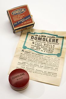 "A jar of ointment, with a box and a poster. The box has the words ""Domolene Brand Stops all skin troubles rashes and irritation The miracle ointment"""