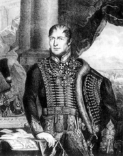 Black and white half-length portrait of General Frimont wearing a full hussar-style dress. His black strands of hair conceal his early baldness. He looks to the left of the viewer and keeps his right hand on a table and his left one on the hip, covered by the pelisse. He has multiple decorations on his chest.
