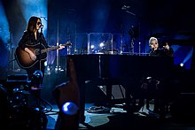 Gaga playing piano and Hilary Lindsey standing opposite to her paying guitar onstage.