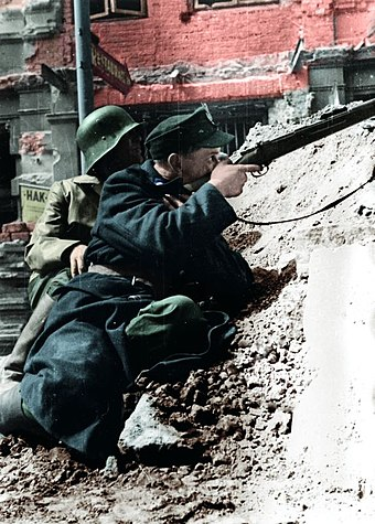 "Soldier from the ""Kilinski"" Battalion pictured aiming his rifle at the German-occupied PAST building, 20 August 1944 Lokajski - Powstancy w Srodmiesciu (1944).jpg"