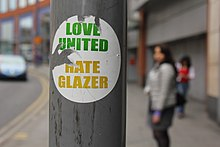 "A photograph of a portion of a lamppost with a torn sticker that reads ""Love United"" in green above ""Hate Glazer"" in yellow."