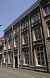 foto van Huis met brede lijstgevel, rijk versierd in Regencestijl.