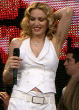 The front profile, up to the waist, of a middle-aged blond woman. She is wearing a white, sleeveless coat and white pants. Her hair is middle-parted and in locks around her face. She is holding a microphone in her right hand while her left hand is placed behind her head. She is smiling looking down. Behind her a video screen is visible whose picture is red.