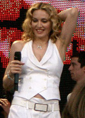 The front profile, from the waist up, of a middle-aged blond woman. She is wearing a white, sleeveless coat and white pants. Her hair is parted in the middle and is in locks around her face. She is holding a microphone in her right hand while her left hand is placed behind her head. She is smiling looking down. Behind her a video screen is red.