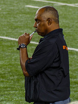 Color photograph of African-American man (Marvin Lewis) wearing black sport shirt, standing on football sideline and holding a capped Sharpie marker to his lips.