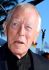 A profile image of Max von Sydow. An elderly Caucasian man with short white hair. He is facing forwards while looking off to the left, with a slight, open-mouthed smile.