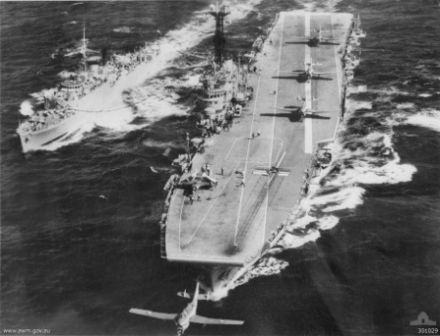 Aerial view of an aircraft carrier and a frigate sailing in close formation. Three propeller aircraft are lined up on the deck of the carrier, while a fourth has just been launched from the catapult.