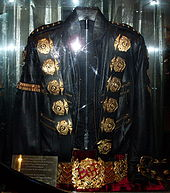 A black jacket with five round golden medals on  its left and right shoulder and a gold ban on its left arm sleeve. The  jacket has two belt straps on the right bottom sleeve. Underneath the  jacket is a golden belt, with a round pendant in the center of it. There  is a red light reflecting on the jacket and belt as well as a gold  squared plat on the left side of the jacket and belt.