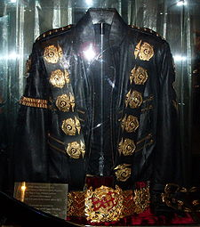 A Black Jacket With Five Round Golden Medals On Its Left And Right Shoulder  And A