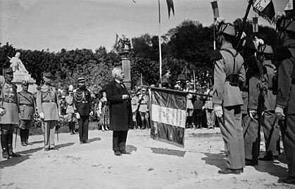 Zwart-witfoto van een ceremonie in aanwezigheid van een man in burgerkleding, grijswit haar, grijze snor, vlinderdas, zwarte jas en jas, zijn blik gericht op soldaten, van wie één een horizontale vlag vasthoudt