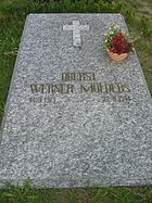 "A marbled-grey stone slab, lying flat on the ground, surrounded by grass and weeds, bearing the golden inscription ""Oberst Werner Mölders 18.3.1913–22.11.1944"" just below the centre of the slab. Above the inscription, there is a small Christian cross and a terracotta bowl with flowers towards the right-hand edge of the slab."