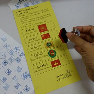 2015 Myanmar general election - A ballot paper and rubber stamp in voting booth