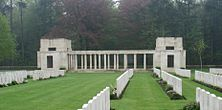 A grass lawn divided by rows of white grave stones. A pair of block-like white stone buildings flank a range of columns.
