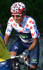 Nairo Quintana wearing a white cycling jersey with red polka dots.