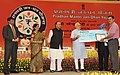 Narendra Modi presenting the award to Shri Sanjay Tiwari for suggesting the name 'Pradhan Mantri Jan Dhan Yojana (PMJDY)', in New Delhi. The Union Minister for Finance, Corporate Affairs and Defence, Shri Arun Jaitley.jpg