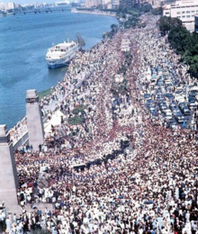 Throngs of people marching in a thoroughfare that is adjacent to a body of water