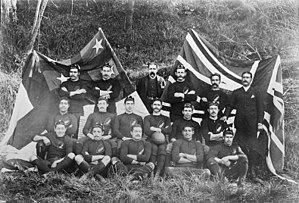 Photo of team players and management all of whom are seated or standing, in three rows, wearing either their playing jerseys with caps, or formal wear.