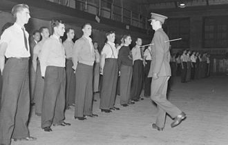 The Canadian Grenadier Guards - An officer of the Canadian Grenadier Guards demonstrates how to turn about to a group of recruits in civilian clothes, 1940.