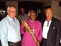 Nobel Peace Prize winner Archbishop Desmond Tutu with SASCOC 2nd Vice President Les Williams, CGF Honorary Legal Advisor Sharad Rao with the Queen's Baton 2010 Delhi.jpg