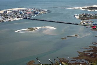 Sinepuxent Bay - The Sinepuxent Bay crossed by the Harry W. Kelley Memorial Bridge, looking south. The southern end of Ocean City, the Ocean City Inlet, the northern tip of Assateague Island, the south inlet jetty, and the Atlantic Ocean are at the top of the image. Skimmer Island is in the left-center and Horn Island is in the right center of the picture, in front of the bridge.