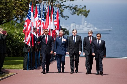 US President Barack Obama, Prince Charles, Brown, Canadian Prime Minister Stephen Harper and French President Nicolas Sarkozy arrive at the Colleville-sur-Mer cemetery to attend a ceremony marking the 65th anniversary of the D-Day landings in Normandy, 6 June 2009. Obama, Prince Charles, Brown, Harper & Sarkozy at Normandy American Cemetery and Memorial 2009-06-06.JPG